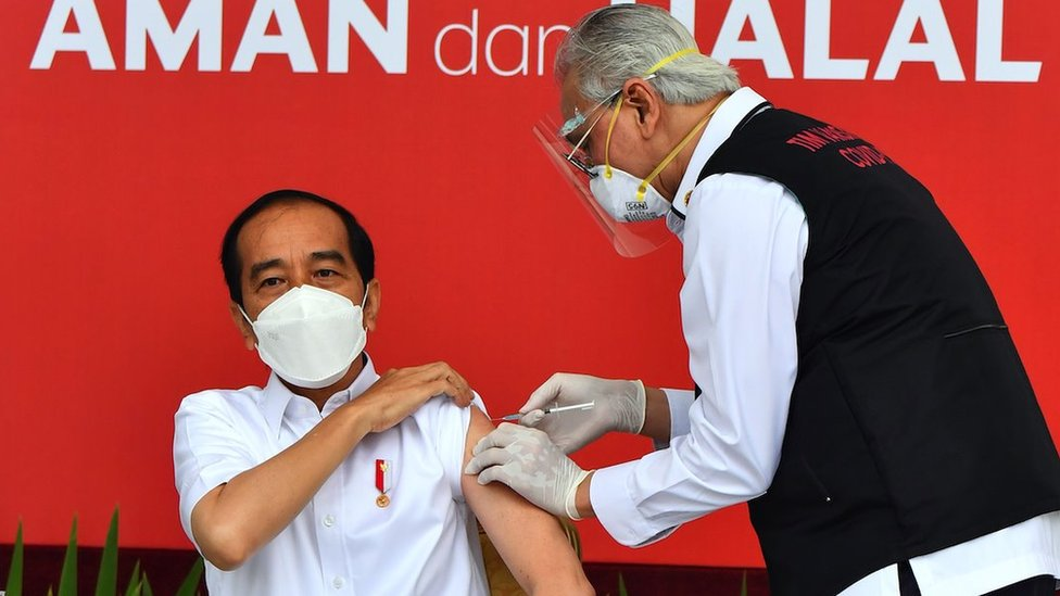 A handout photo made available by the Presidential Palace Indonesia shows Indonesian President Joko Widodo (L) injected with a COVID 19 vaccine by Presidential Doctor Abdul Muthalib (R) at the Presidential Palace in Jakarta, Indonesia, 13 January 2021