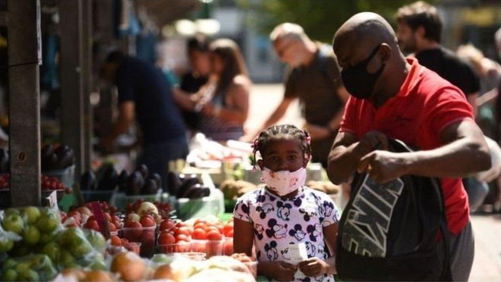 رجل وطفلة يرتديان كمامات وآخرون في سوق