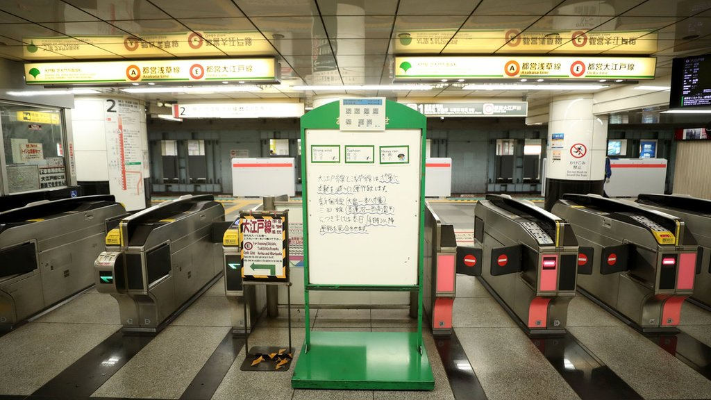 A deserted subway station in Tokyo, with a message board in front of the barriers