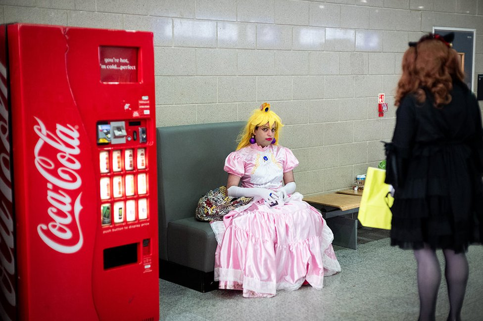A woman dressed as a cartoon character sits and stares