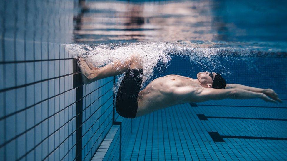 Hombre bajo el agua nadando.