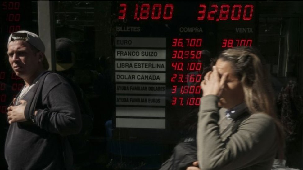 Currency exchange values are displayed in the buy-sell board of a bureau de exchange in Buenos Aires, on August 29, 2018.