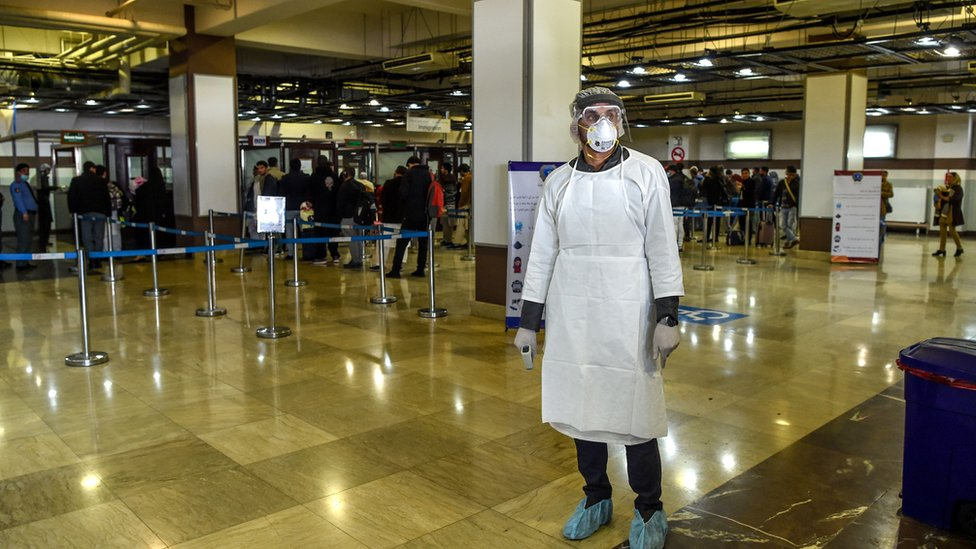 A health services staff member wearing protective gear looks on as he waits to check