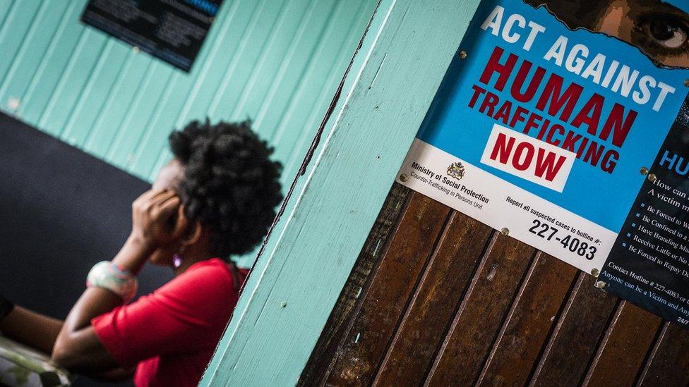 """Un afiche en una oficina de Georgetown, Guyana, que lee, """"Actúa contra el tráfico humano, ahora"""""""