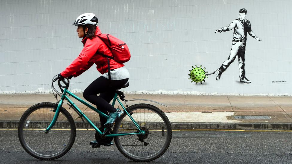 Woman cycling by graffiti showing a man chained to a coronavirus