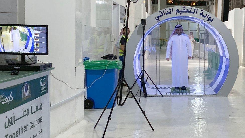 Un hombre pasa por una puerta de esterilización en la entrada de una mezquita en Arabia Saudita.