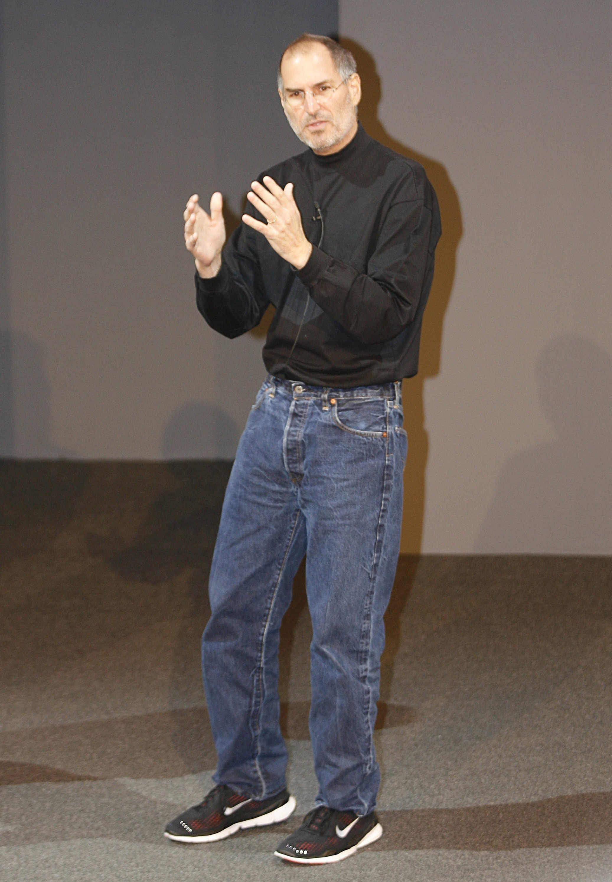 Steve Jobs wearing a black turtleneck sweater, blue jeans and sports shoes at Apple events