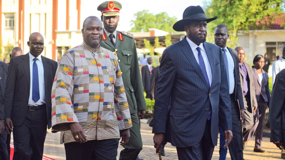 Riek Machar walks alongside President Salva Kiir on the red carpet