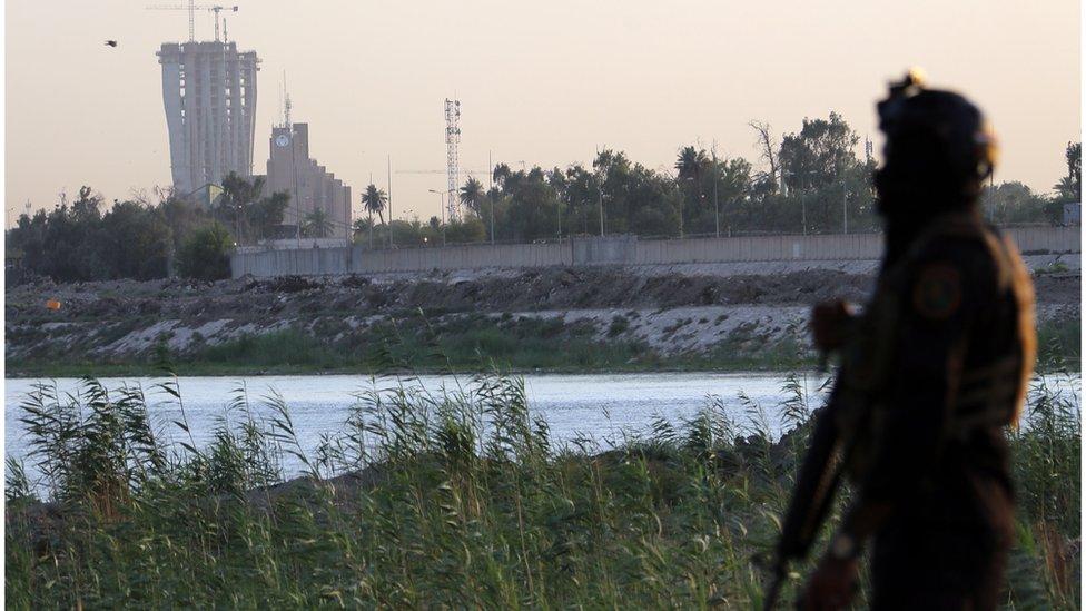 (أرشيف) أحد أفراد الأمن العراقي وفي الخلفية المنطقة الخضراء التي توجد بها السفارة الأمريكية