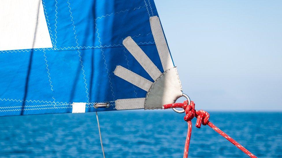 Nudo agarrando vela de barco en mar