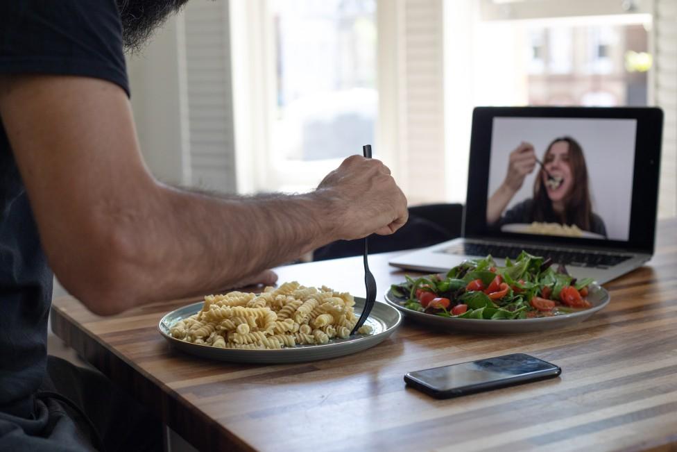 Pareja comiendo con las pantallas