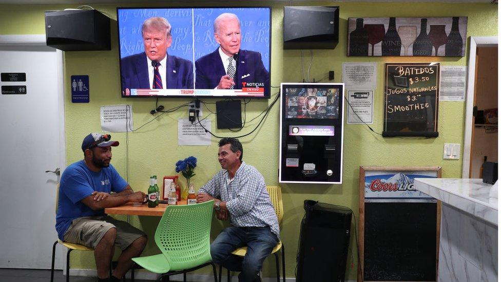 People sitting under screen of Trump Biden debate in Miami, Florida
