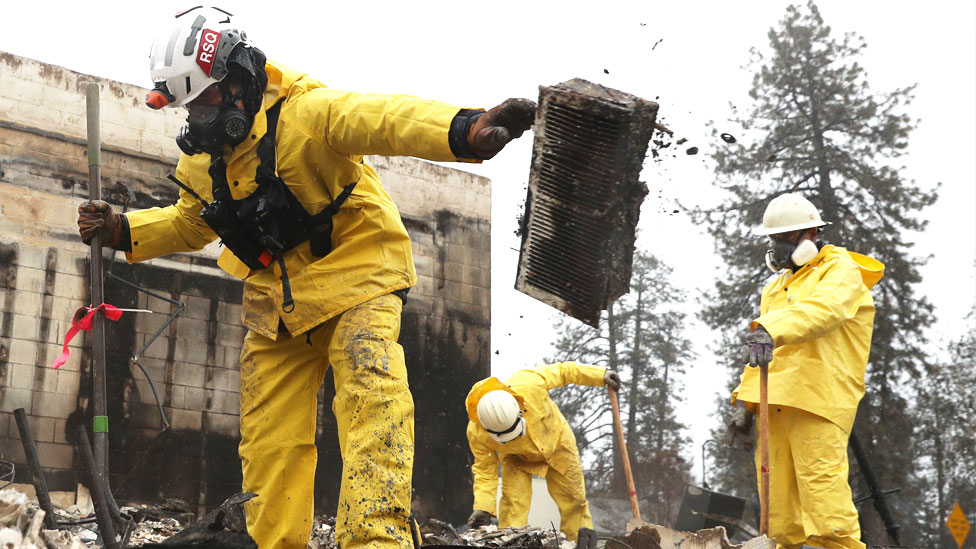 Search and rescue crews dig through the burnt remains of a business as they search for human remains in Paradise, California.