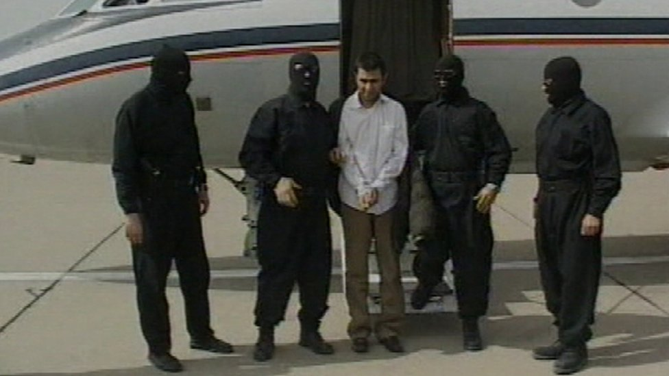هذه الصورة نشرت في 23 فبراير/شباط 2010 من التلفزيون الإيراني الرسمي تظهر زعيم الجماعة ال المتمردين السني عبد الملك ريغي تحت حراسة مسلحة بعد اعتقاله.