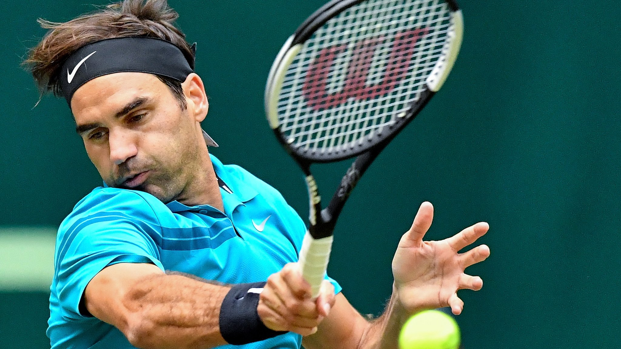 Federer saves two match points to advance in Halle