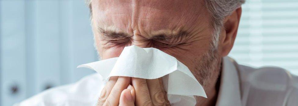 Man sneezing into handkerchief