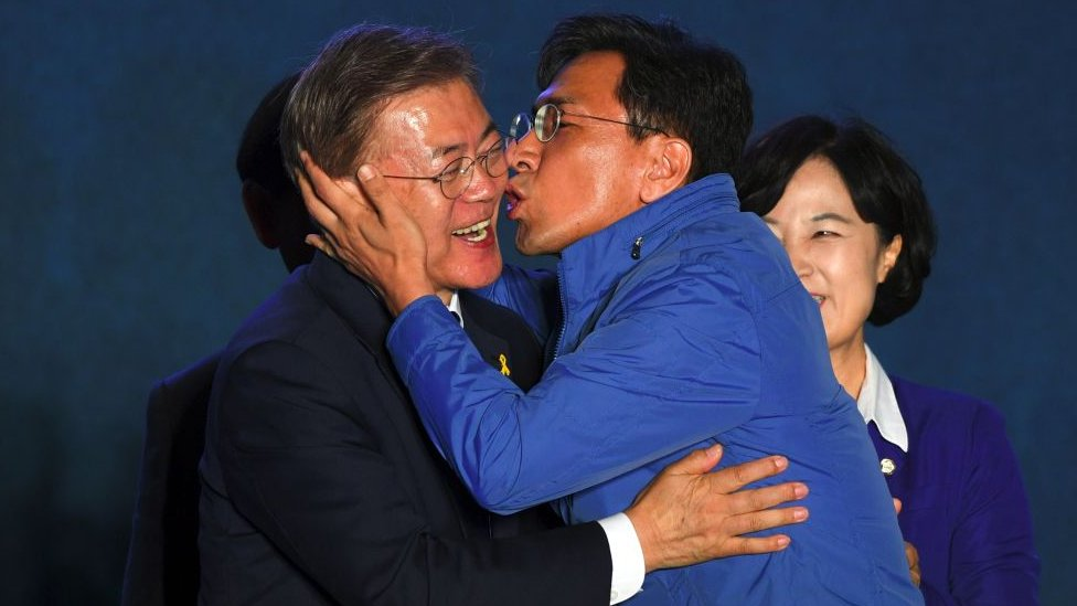 South Korean presidential candidate Moon Jae-in (L) of the Democratic Party receives a kiss from his party member Ahn Hee-Jung (R)