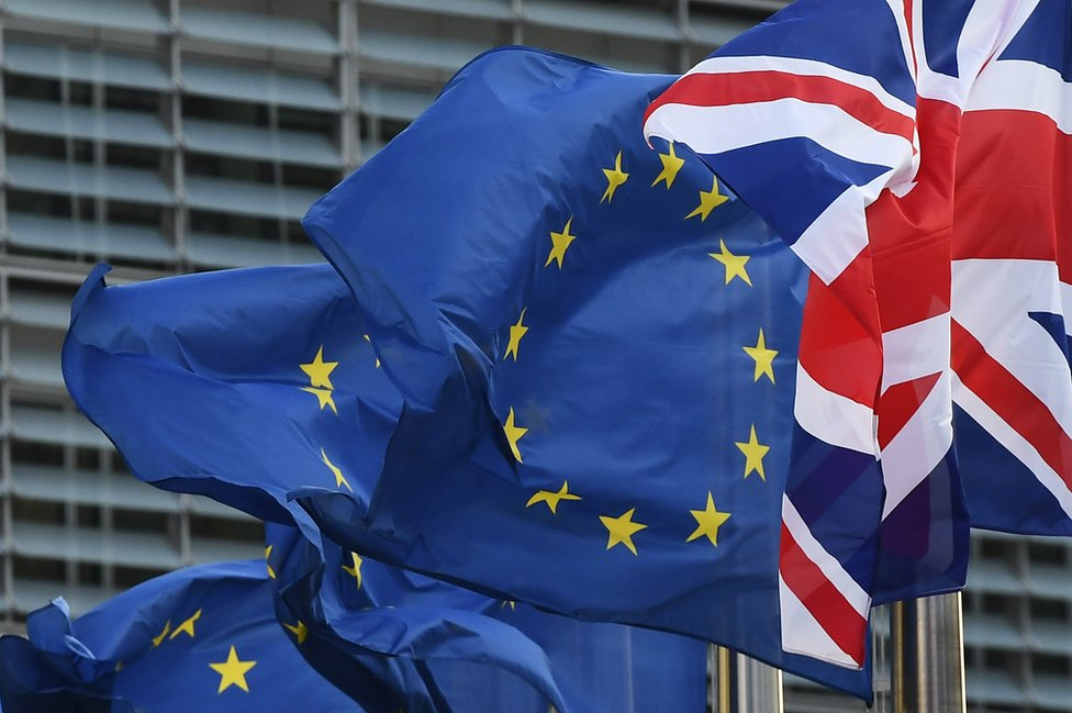 A Union Jack flies next to European Union flags in front of the European Commission, 16 October 2017