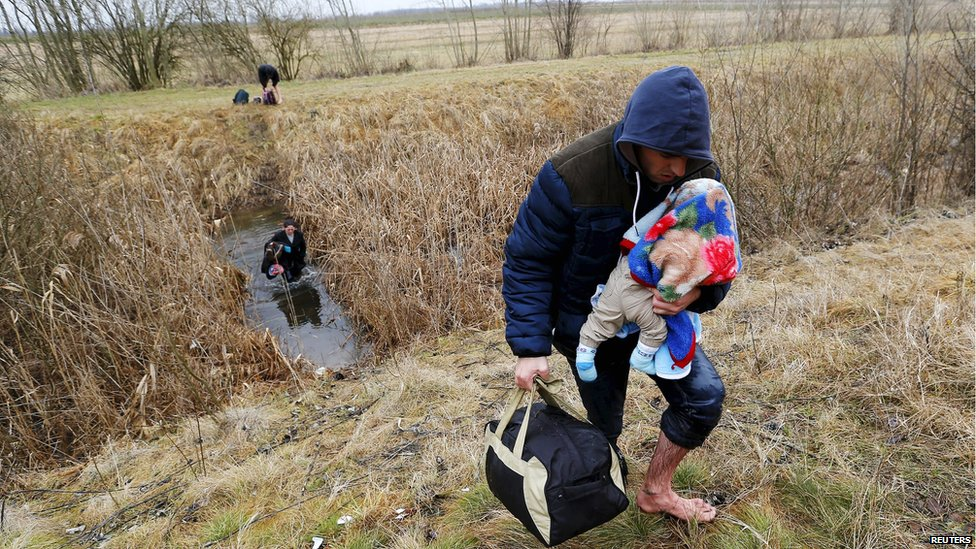 A Kosovar man wades through water while carrying his child as they illegally cross the Hungarian-Serbian border near the village of Asotthalom, Hungary, in this February 6, 2015 file photo