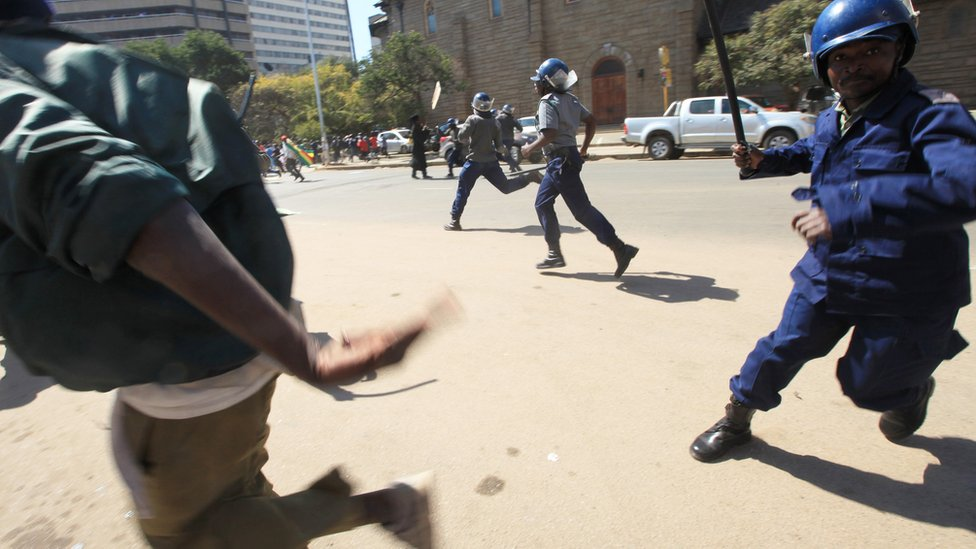 A policeman with a baton chasing a protester in Harare, Zimbabwe - Wednesday 3 August 2016