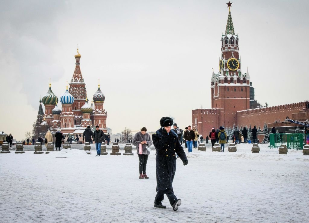 A serviceman walks in front of St Basil's Cathedral and the Kremlin