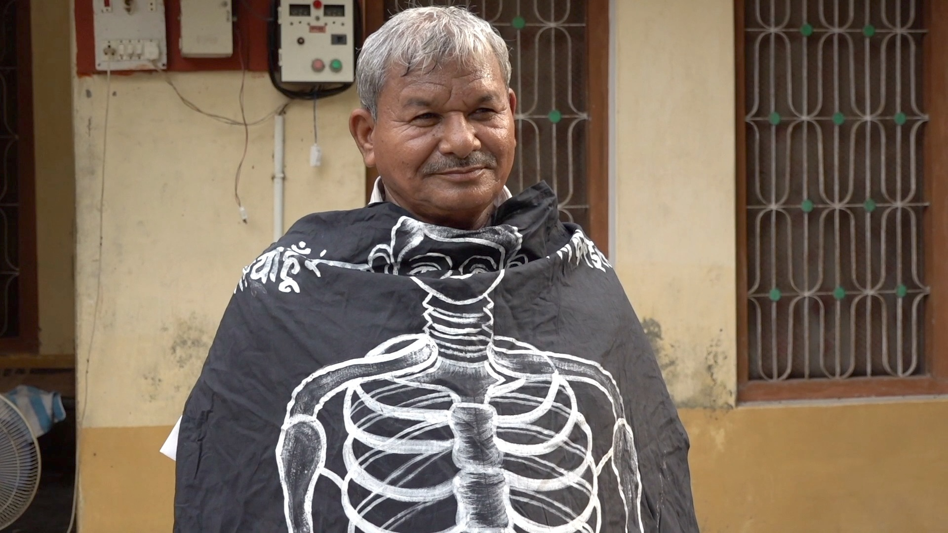 Lal Bihari Mritak envuelto en una pancarta de la Asociación de Muertos Vivientes
