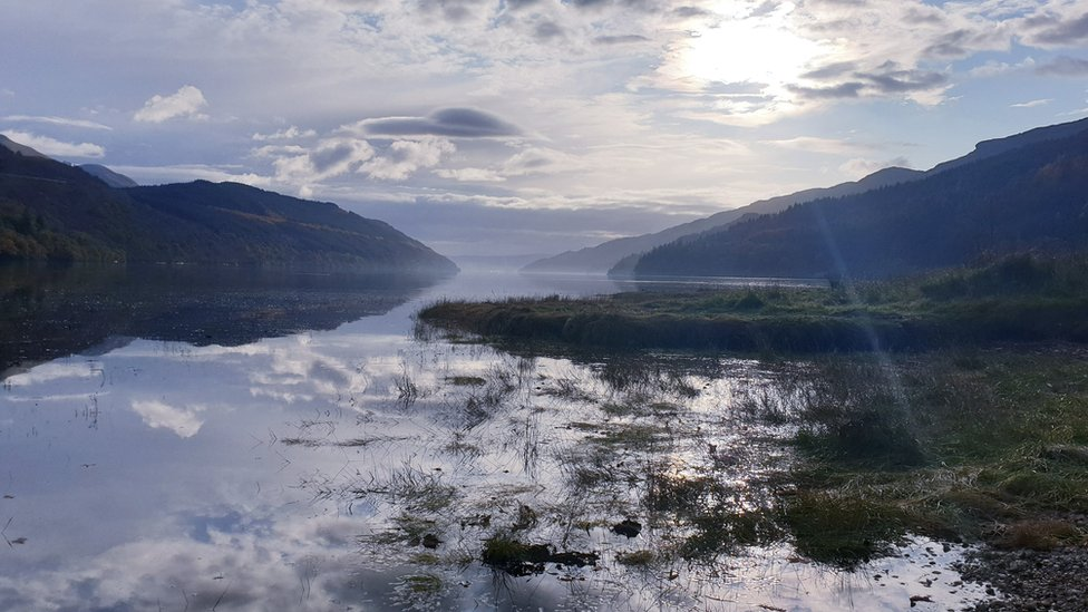 A landscape and reflections on the water at Loch Long