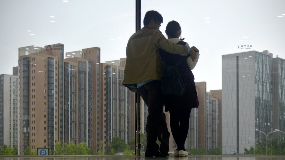 A couple look out of a window at blocks of flats in Beijing