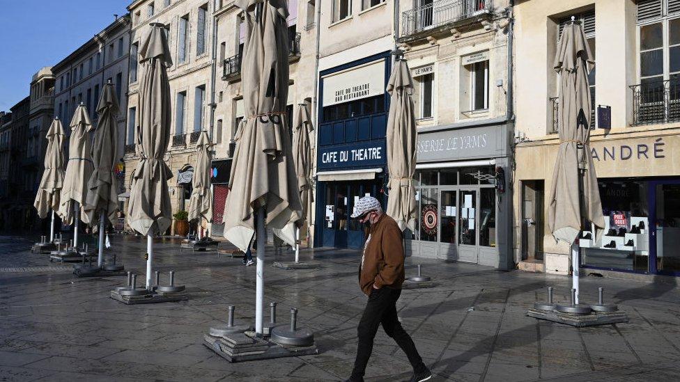 Hombre caminando ante restaurantes cerrados en Montpellier, Francia.