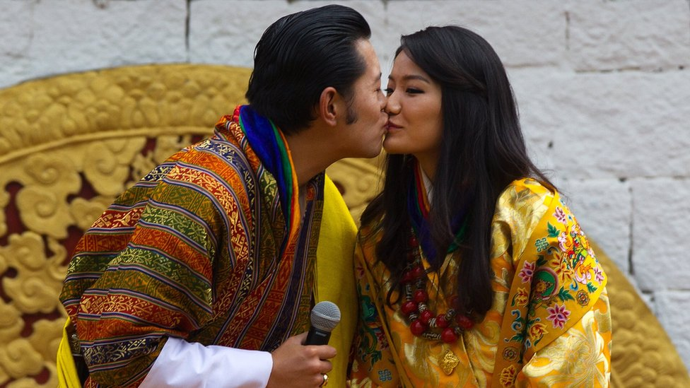The king of Bhutan and his wife share a kiss