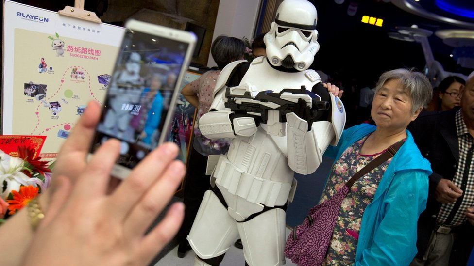 """A Chinese woman poses for a smartphone photo with a worker dressed in a storm trooper costume at the Wanda Mall at the Wanda Cultural Tourism City in Nanchang in southeastern China""""s Jiangxi province, Saturday, May 28, 2016."""