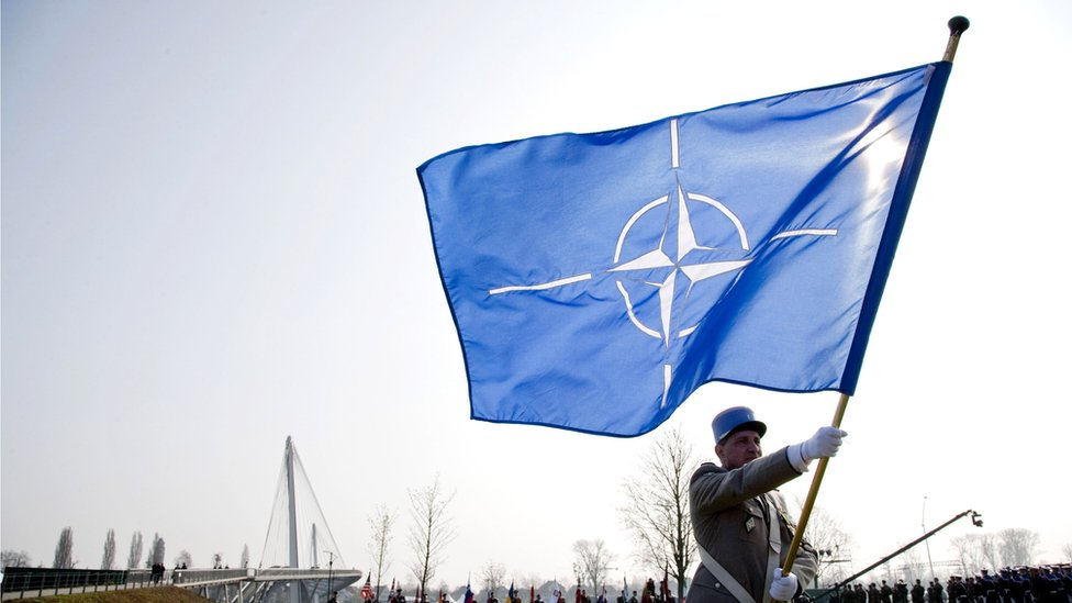 Soldier carrying a Nato flag