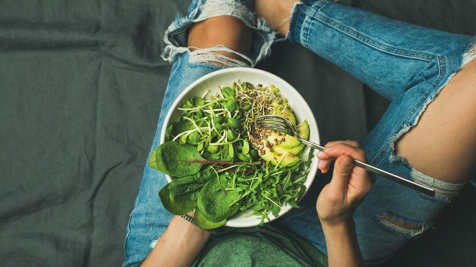 Chica comiendo ensalada.