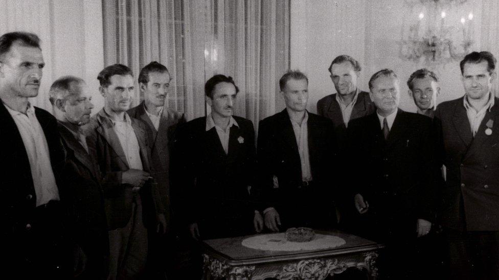 Grupa radnika okupljena oko Tita u prijemnoj prostoriji