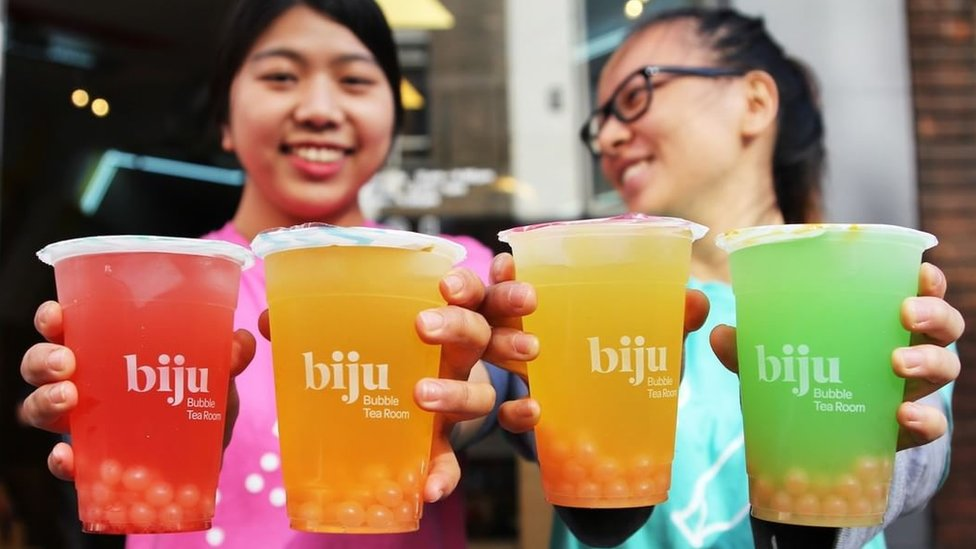 Two girls holding Biju bubble teas