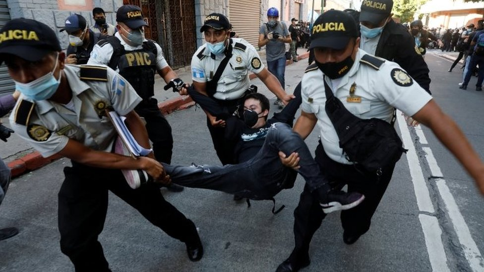 Police officers carry a demonstrator in Guatemala City. Photo: 21 November 2020