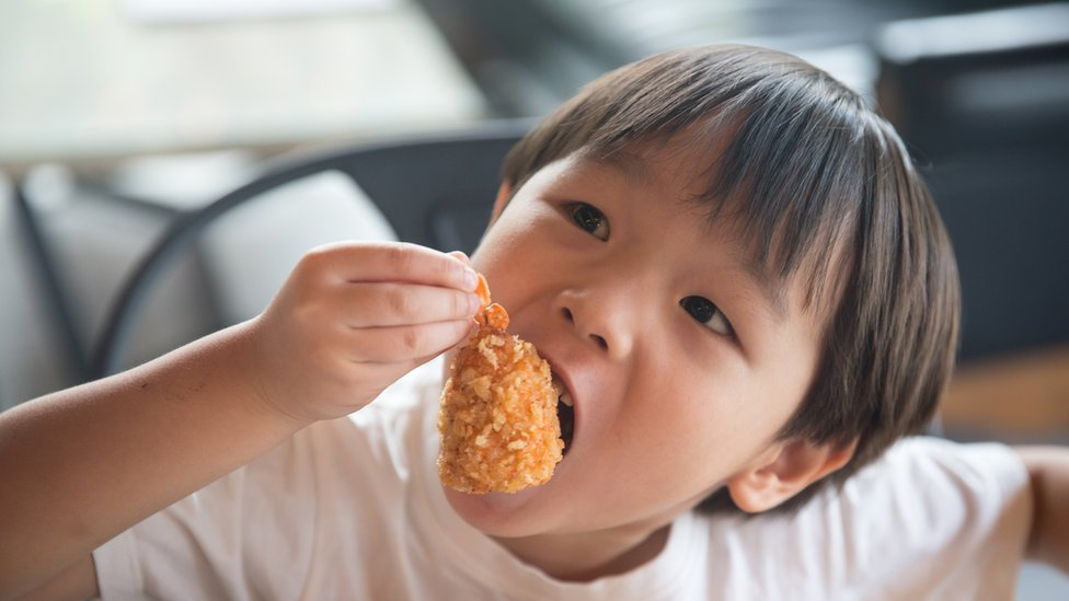 niño comiendo alitas de pollo