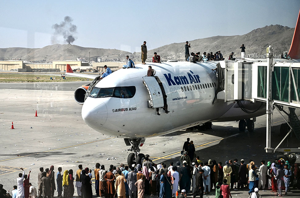 Afghan people climb atop a plane as they wait at the Kabul airport on 16 August 2021