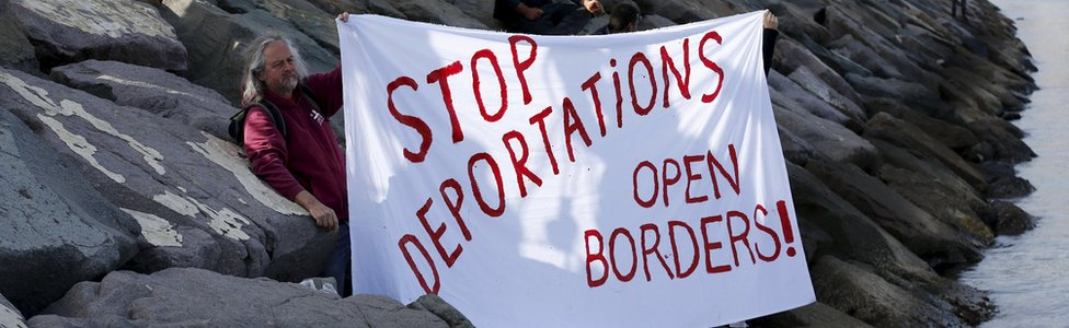 "Activists hold a banner which says ""Stop deportations, open borders"" in the Turkish coastal town of Dikili"