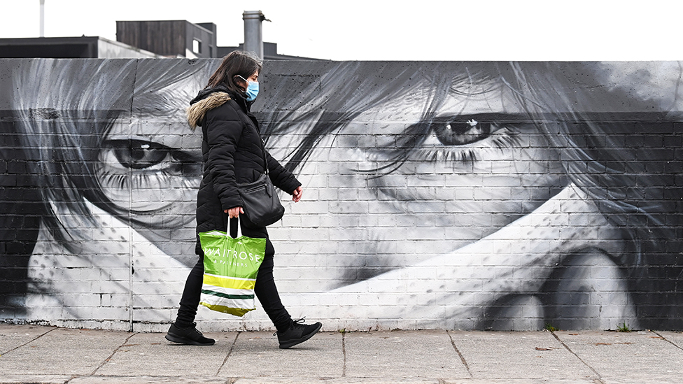 People walk past a mural showing a person in a face mask in London - 15 January 2021