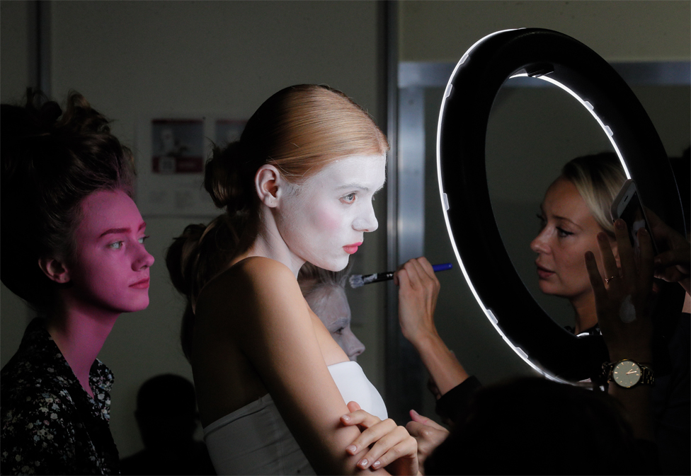 Models stand and wait as they have full-face make-up applied by a make-up artist