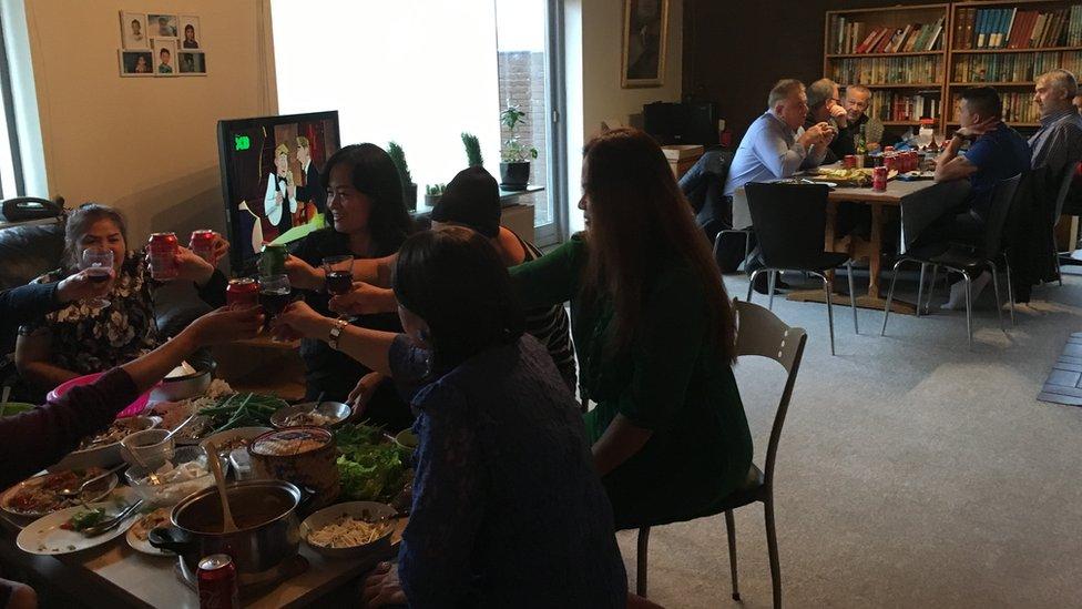Mujeres tailandesas sentadas separadas de hombres daneses durante una comida.