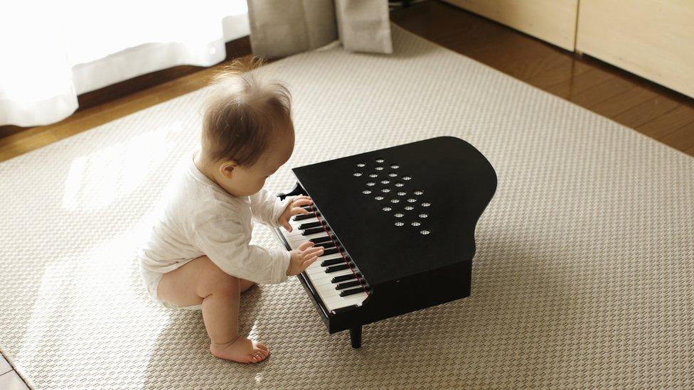 bebé con un piano de juguete.