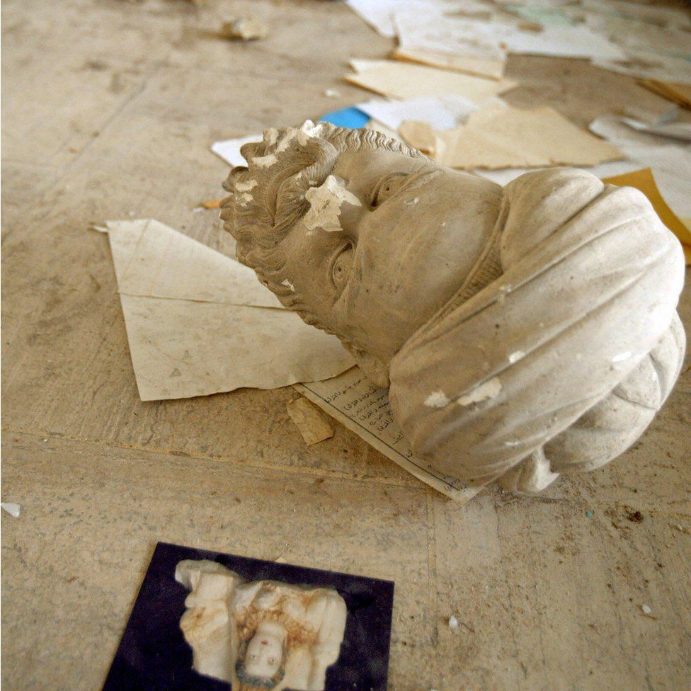 Smashed statue on floor of looted museum