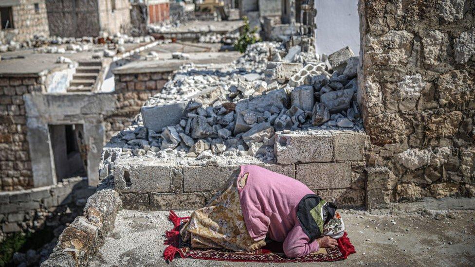 Una mujer entre los edificios destrozados en Idlib, Siria.