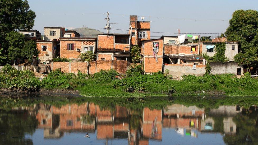 Casas precárias, sem pintura, na beira de canal poluído no Rio de Janeiro
