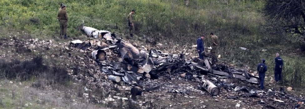 Israeli soldiers inspect the remains of an Israeli F-16 fighter jet that was shot down after being hit by Syrian anti-aircraft fire, in northern Israel, 10 February 2018