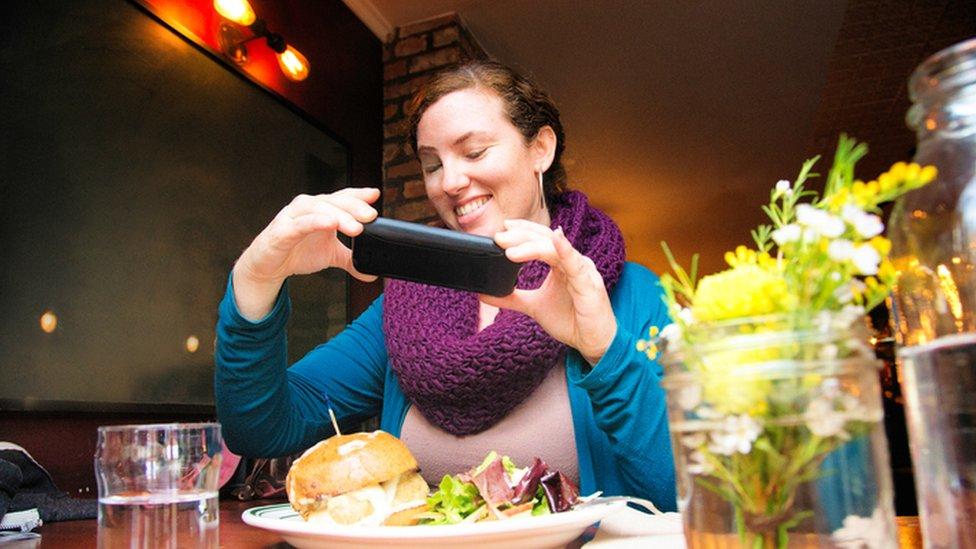 Mujer fotografiando su comida