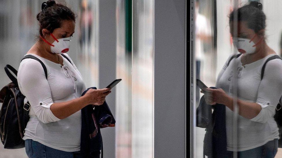 Mujer con mascarilla leyendo su celular.
