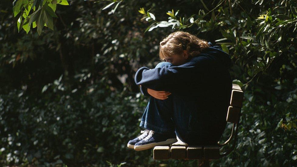 Devojčica usamljeno sedi na klupi